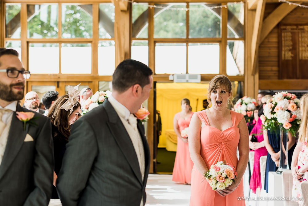 bridesmaid pulling funny face at groom