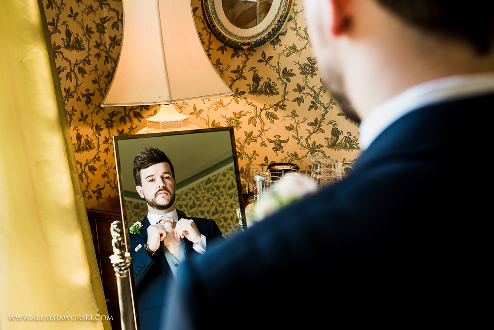 Groom looking in mirror at Ardington House