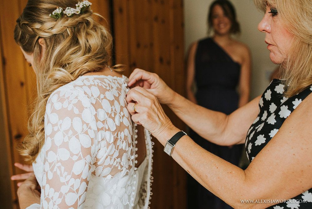 mum helping daughter button up the wedding dress