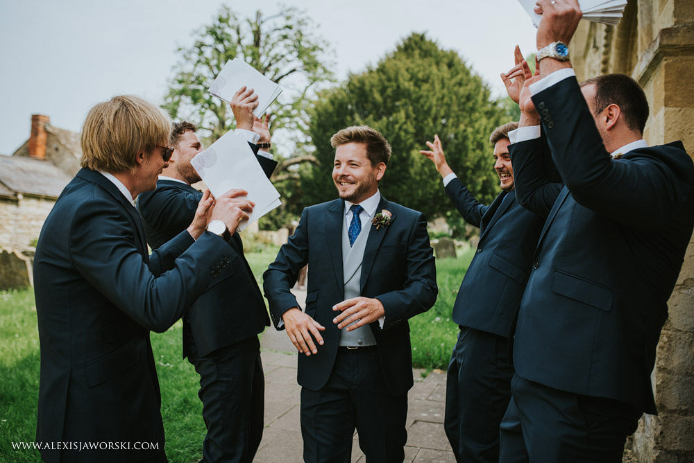 groom having fun with groomsmen at the church