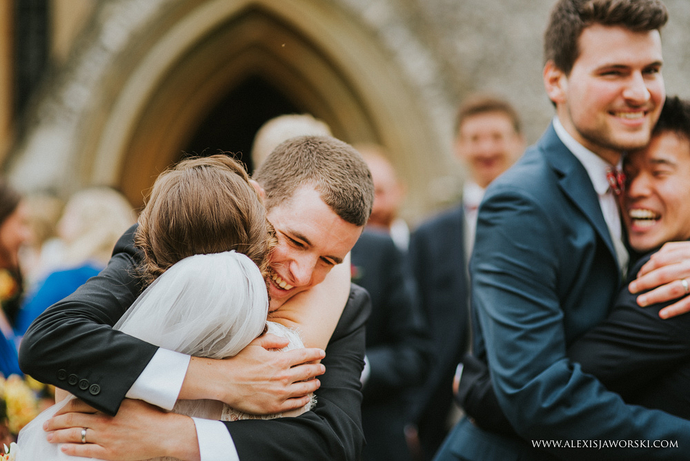 bride and groom getting hugs from friends