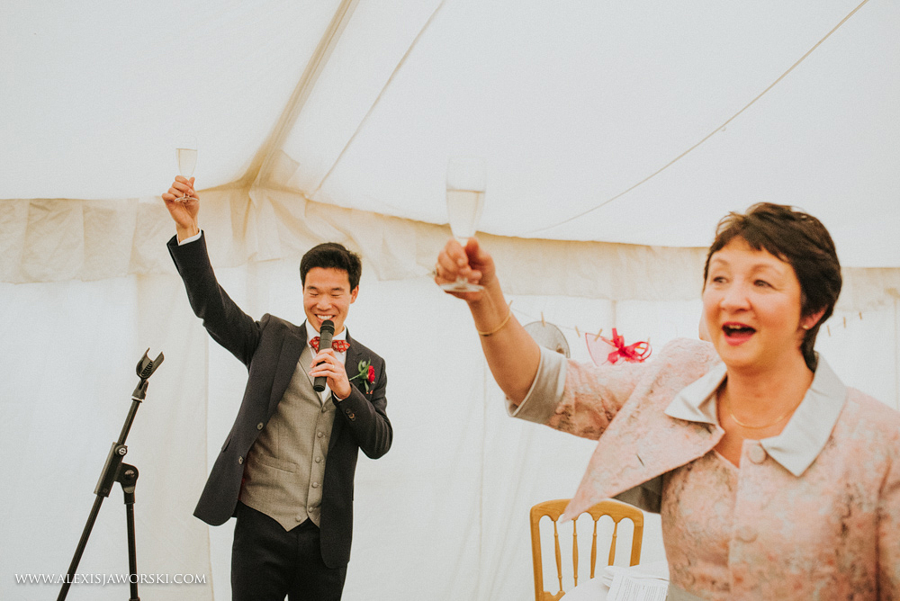 groom and mother of the bride raising their glasses