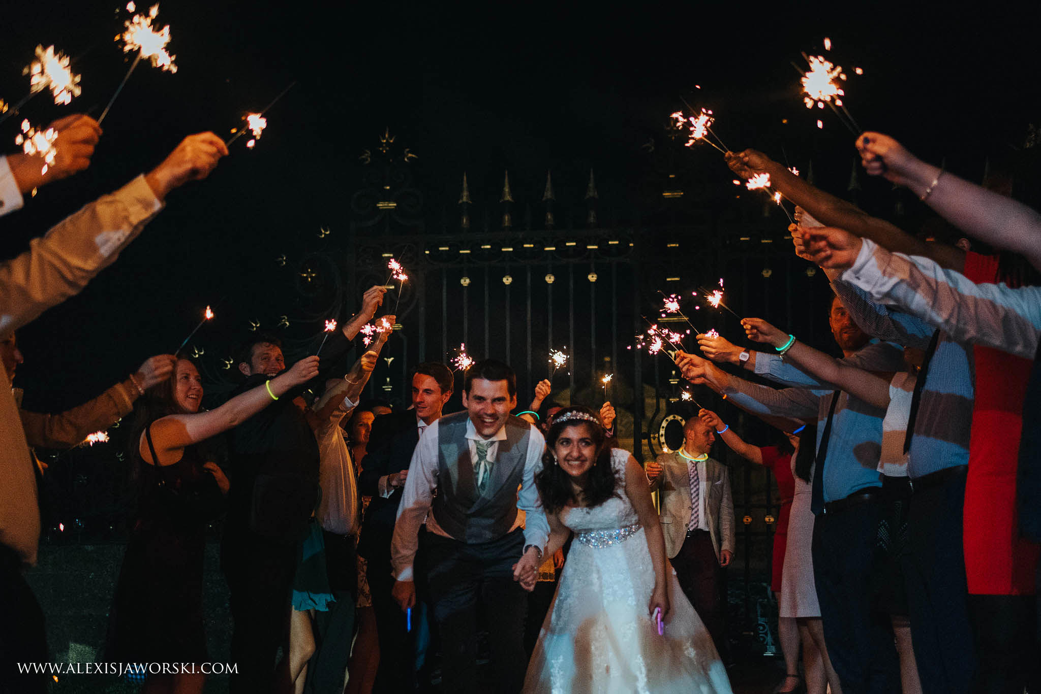 bride and groom walking through sparklers tunnel