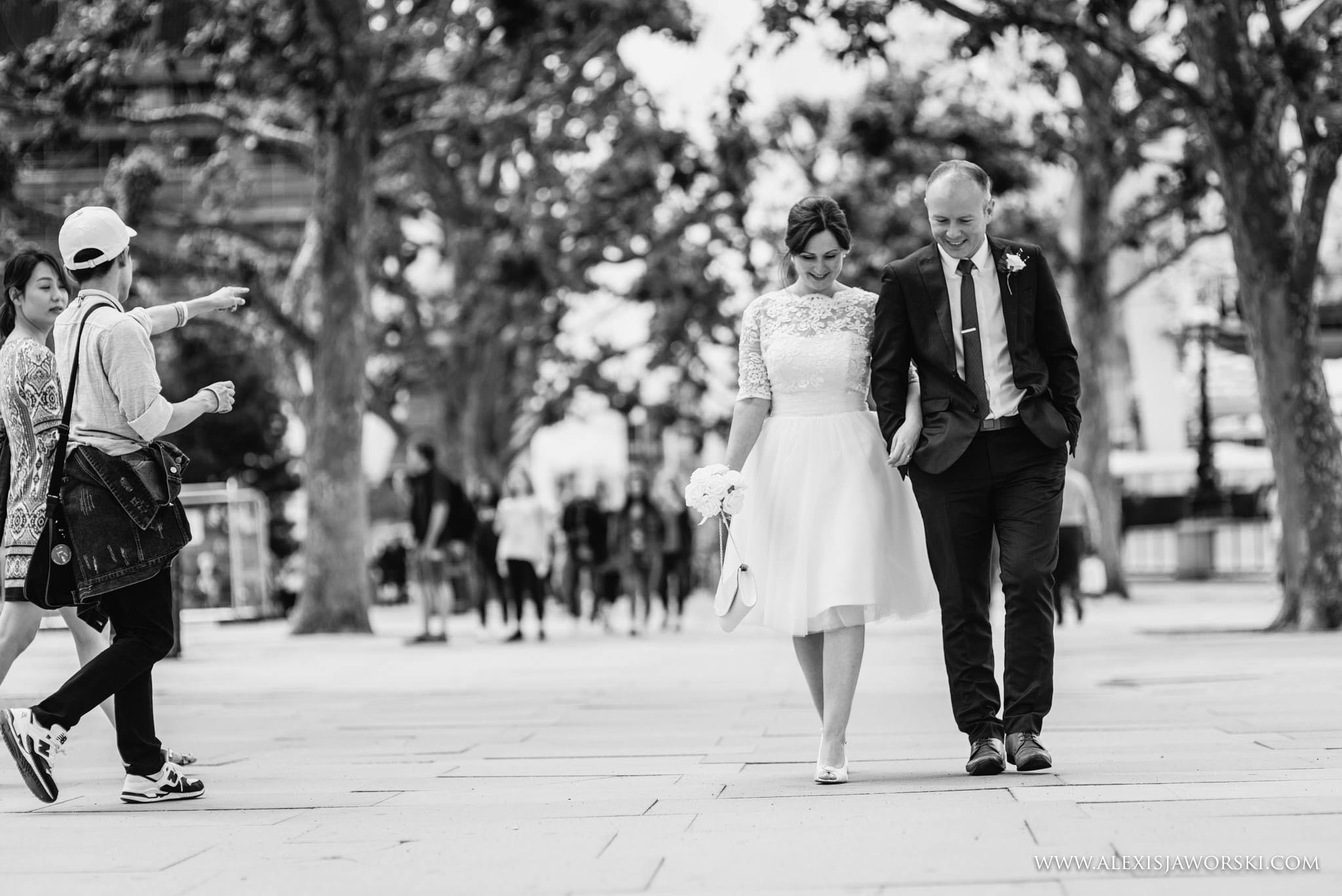Casual black and white portrait of the bride and groom walking