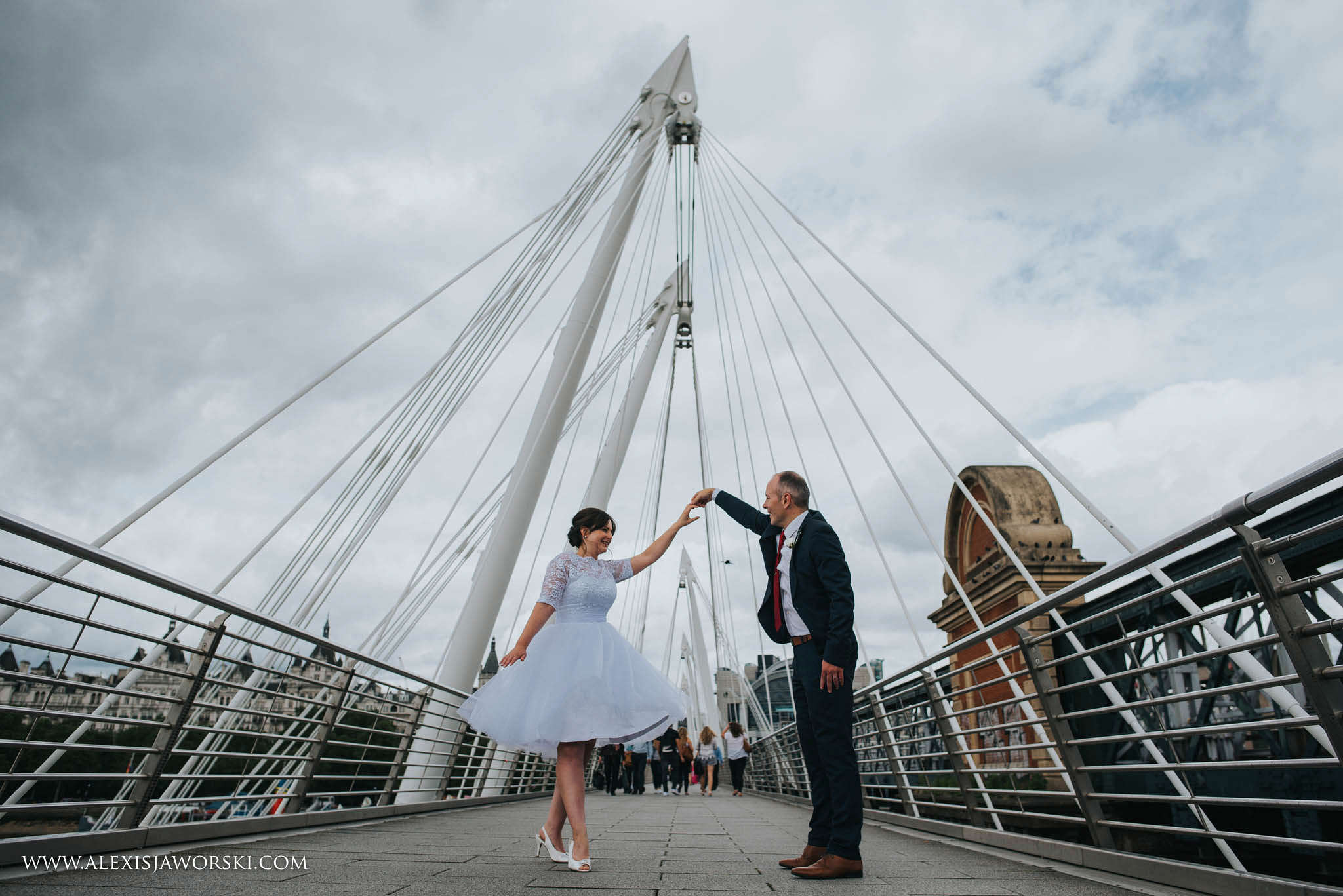 Bride and groom dancing on bridge