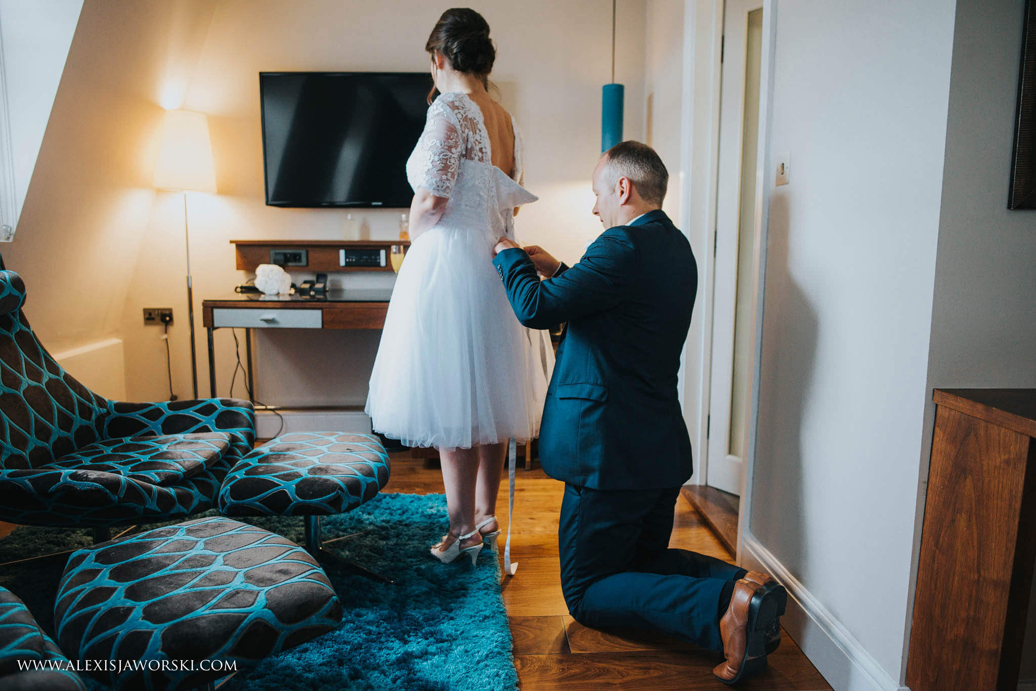 Groom helping bride putting the dress on