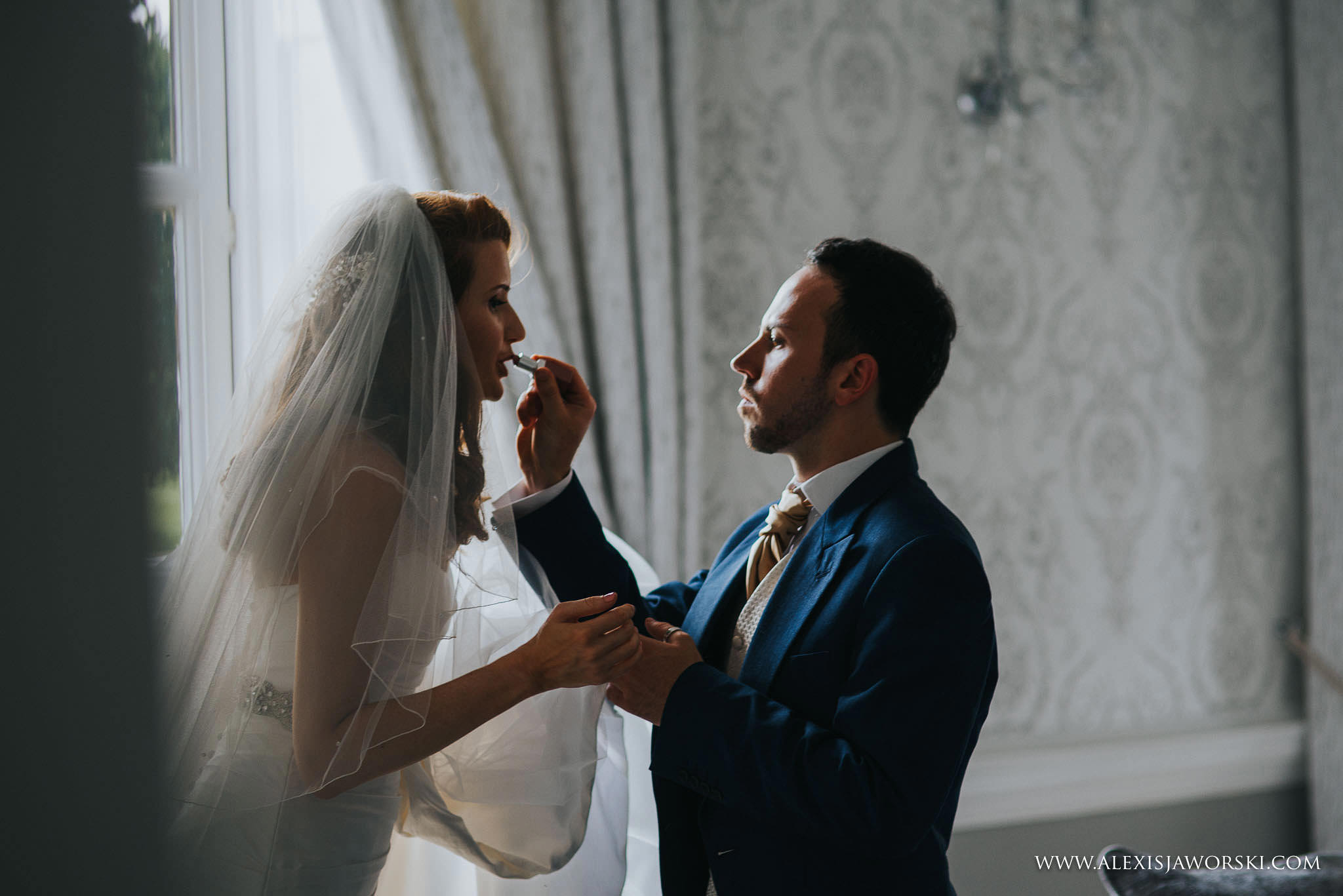 Man of honor helping bride with make up