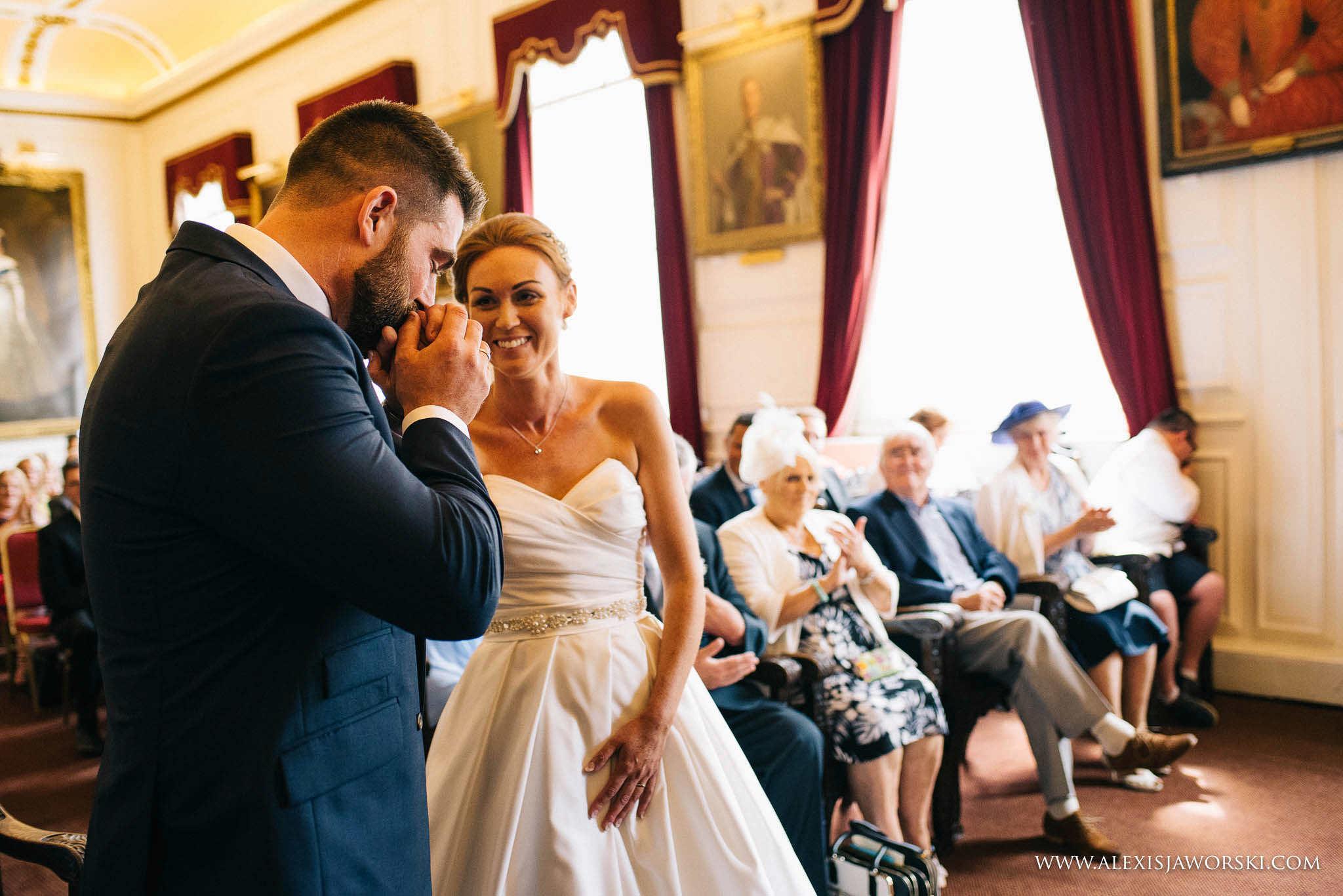 groom kisses bride hand