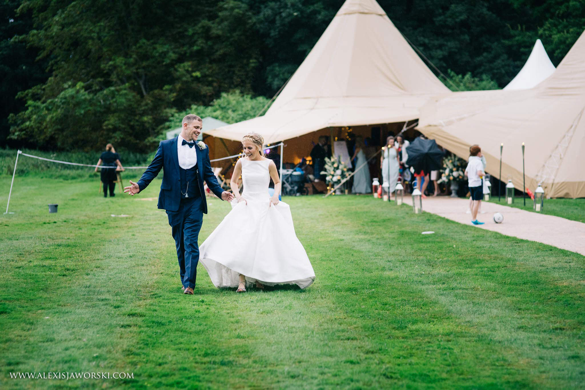 candid portrait of bride and groom with tipi in background