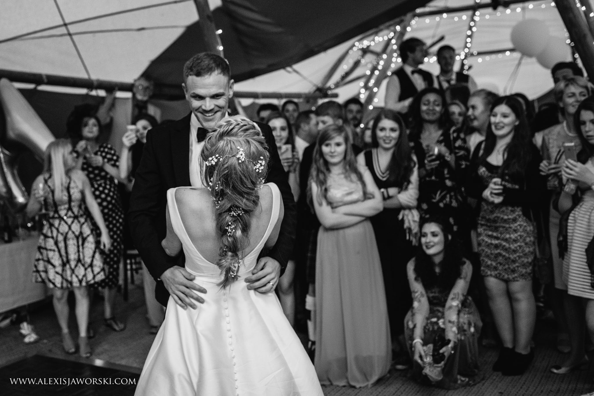 brid eand groom dancing with guests looking on