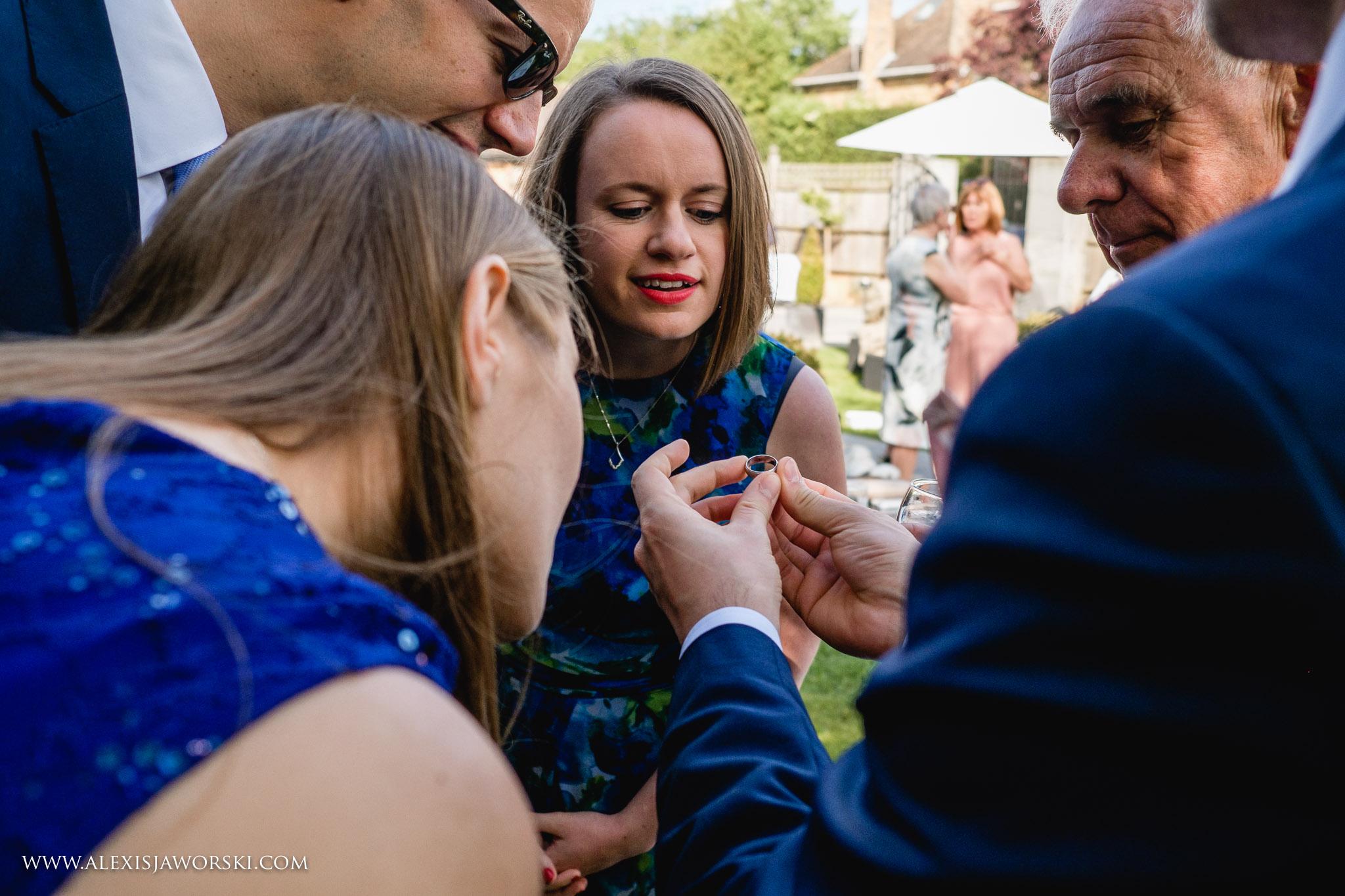 guests looking at groom wedding ring