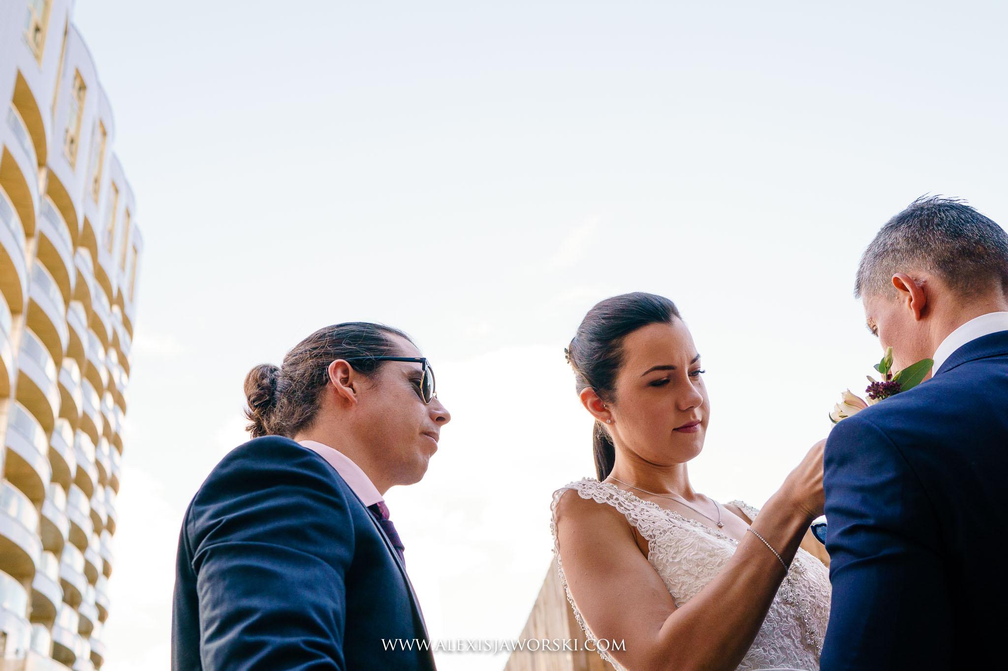 bride helping groom with flower