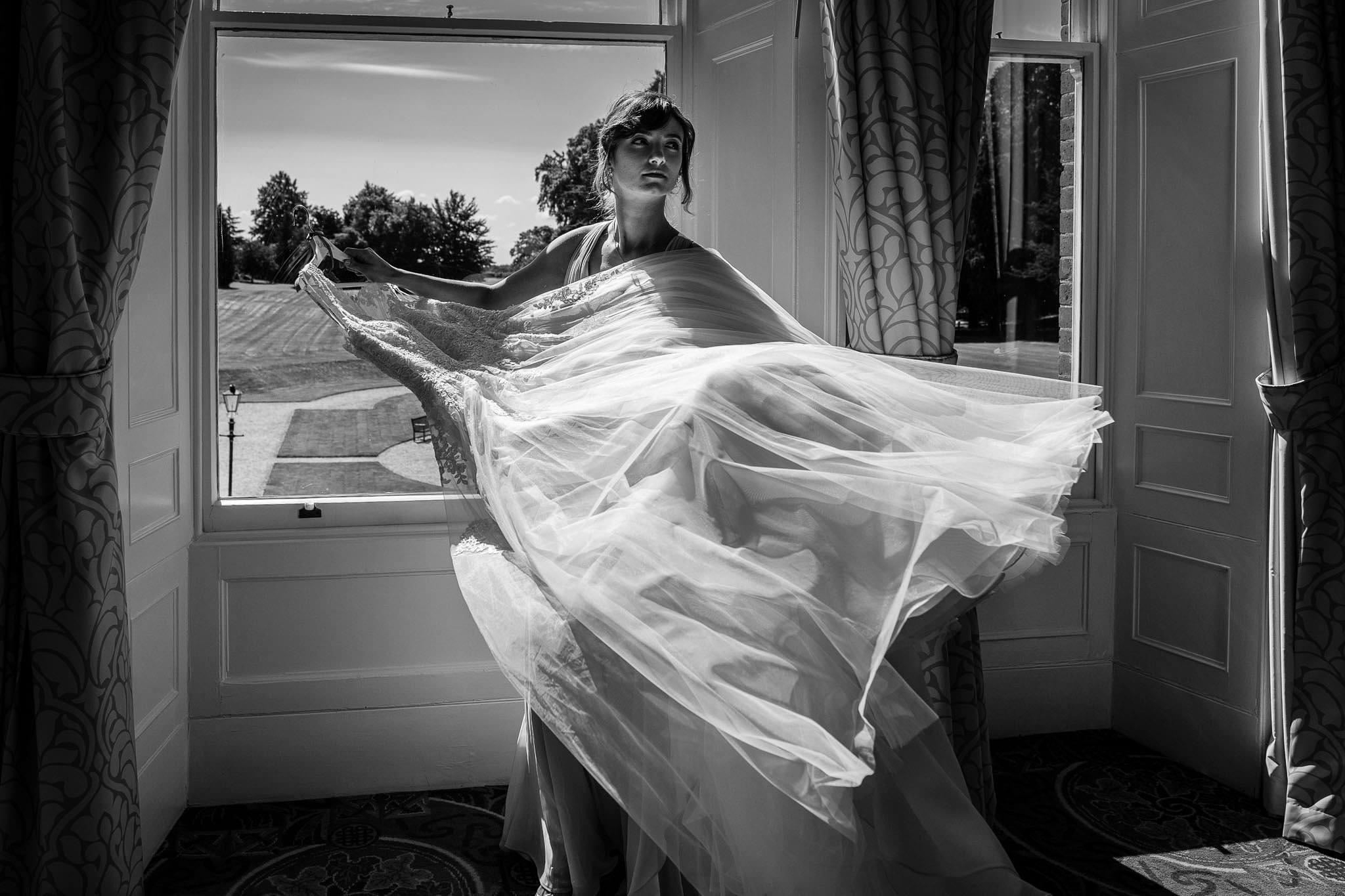 bridesmaid holding dress
