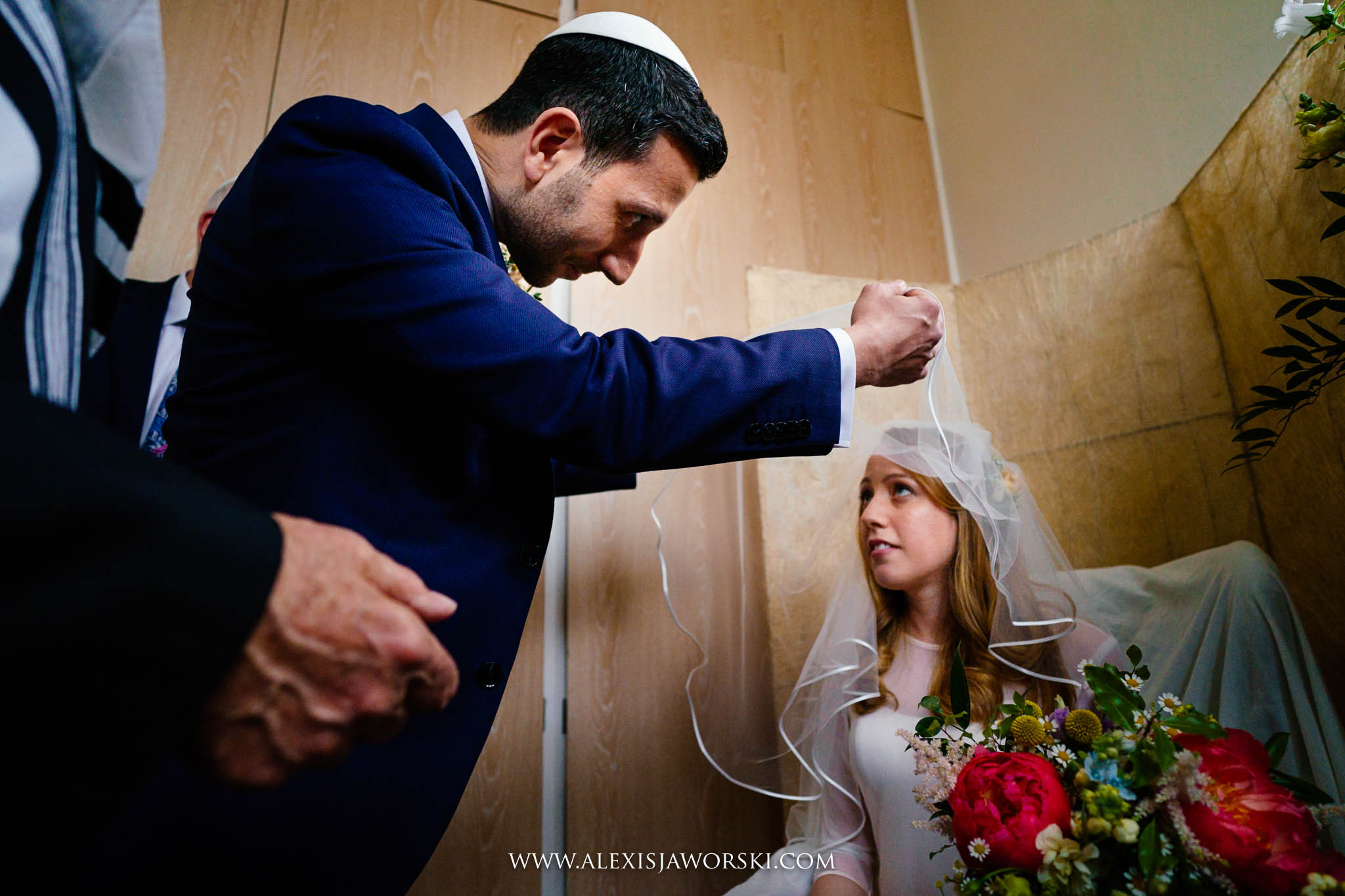 Groom lifting bride's veil