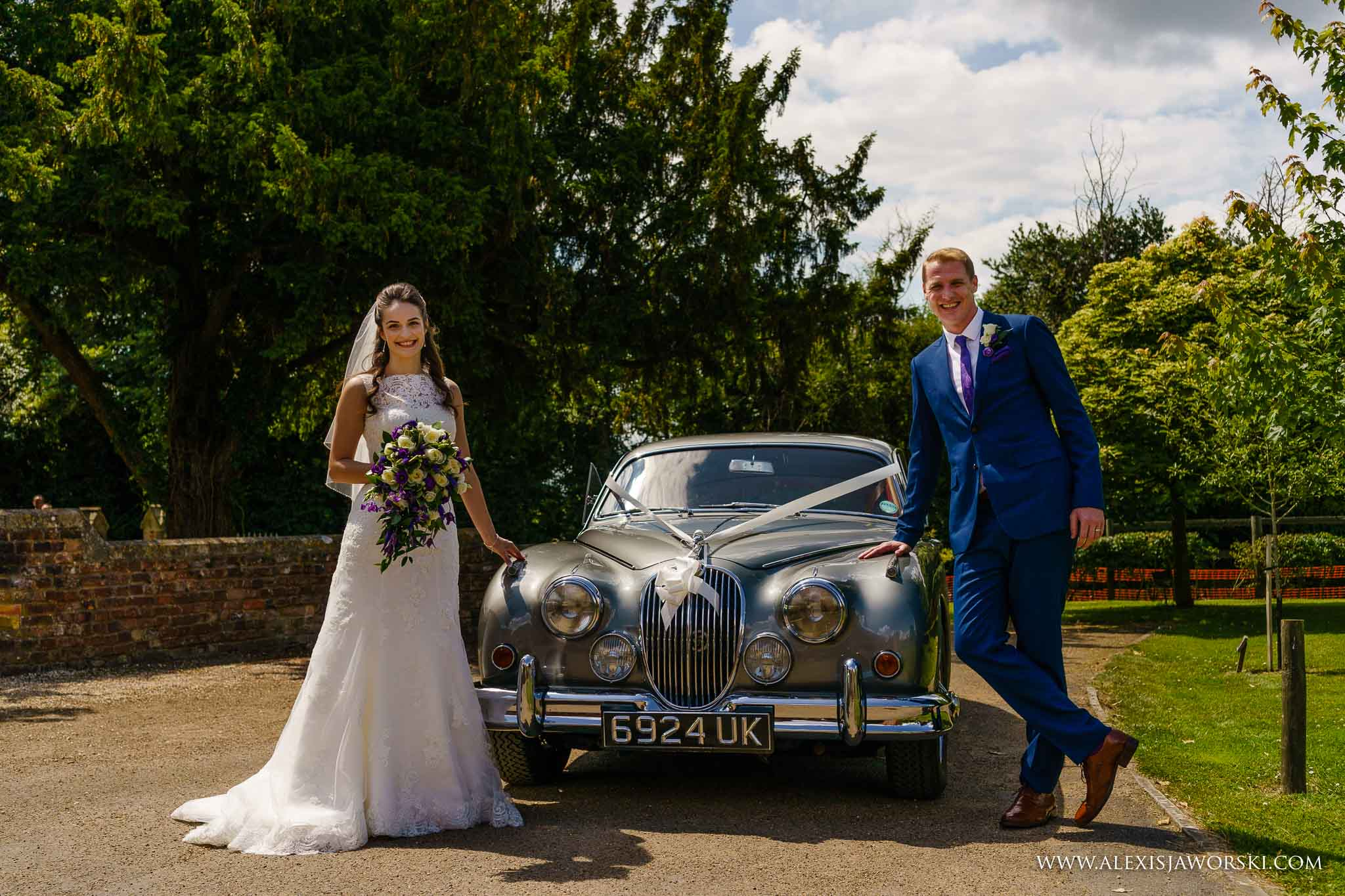 bride and groom by wedding car